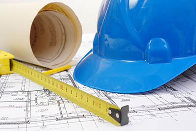 Closeup of blue hard hat, yellow pencil, measuring tape and building plans.