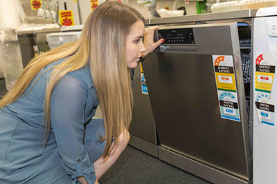 Woman in a store, looking at the Water Rating label on a dishwasher.